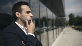 Homem de negócios interessado considerável que espera alguém fora o prédio de escritórios