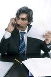Homem de negócios interessado, virado no telefone Fotografia de Stock Royalty Free
