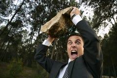 Homem de negócios irritado ao ar livre, pedra grande nas mãos Fotos de Stock