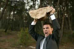 Homem de negócios irritado ao ar livre, pedra grande nas mãos Imagem de Stock