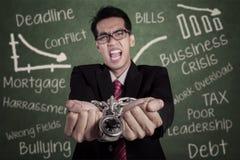 Homem de negócios irritado com as mãos acorrentadas na classe Imagem de Stock