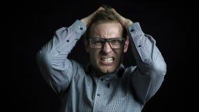 Homem de negócios irritado com gritaria dos vidros isolado em um fundo preto filme