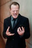 Homem de negócios irritado, gritando no telefone de pilha Imagem de Stock Royalty Free