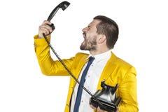 Homem de negócios irritado que grita ao monofone de telefone fotografia de stock royalty free