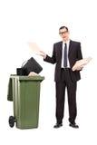 Homem de negócios irritado que joga seu material no lixo Fotografia de Stock