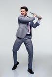 Homem de negócios irritado que tenta despedaçar seu portátil Fotografia de Stock Royalty Free