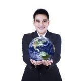 Homem de negócios isolado que guarda um globo Imagens de Stock