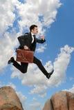 Homem de negócios Jumping From Rock Imagem de Stock Royalty Free