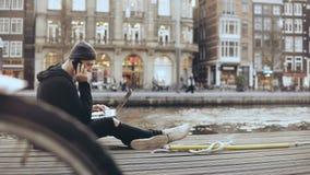 homem de negócios 4K caucasiano com portátil fora Equipe a fala no telefone que senta-se na rua, Amsterdão empreendedor vídeos de arquivo