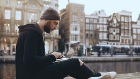 homem de negócios 4K que senta-se com um portátil perto do rio Trabalhador criativo das artes feliz e bem sucedido Amsterdão, Paí video estoque