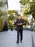 Homem de negócios latino-americano pensativo novo que anda fora do prédio de escritórios fotos de stock royalty free
