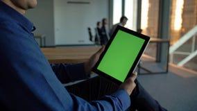 Homem de negócios latino-americano que guarda um tablet pc preto com tela verde video estoque