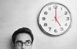 Homem de negócios Looking At Clock na parede de madeira Fotografia de Stock