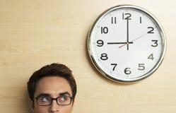 Homem de negócios Looking At Clock na parede de madeira no escritório Foto de Stock Royalty Free