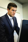 Homem de negócios Looking At Computer Imagens de Stock
