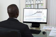 Homem de negócios Looking At Graph no computador Fotos de Stock Royalty Free