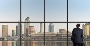 Homem de negócios Looking Out From uma janela do escritório, amanhecer imagens de stock