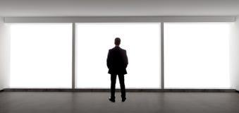 Homem de negócios Looking Out uma janela grande Fotografia de Stock Royalty Free