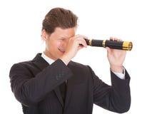 Homem de negócios Looking Through Telescope Fotos de Stock Royalty Free