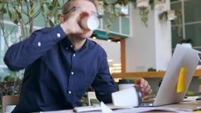 Homem de negócios louco engraçado com café bebendo do apego da cafeína e datilografia no portátil muito rapidamente no escritório video estoque