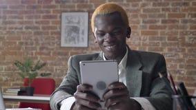 Homem de negócios louro afro-americano novo que consultam na tabuleta e sorriso, sentando-se no escritório moderno, seguro e filme