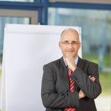 Homem de negócios maduro With Arm On Chin By Flipchart Foto de Stock Royalty Free