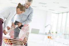 Homem de negócios maduro com a mulher de negócios nova que envolve cadeiras no plástico no escritório novo imagem de stock