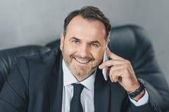 homem de negócios maduro feliz que fala o telefone e pela vista foto de stock royalty free