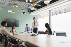 Homem de negócios maduro Giving Boardroom Presentation aos colegas na sala de reunião imagem de stock