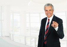 Homem de negócios maduro no ajuste chave alto do escritório que aponta na câmera imagem de stock