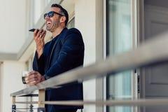 Homem de negócios maduro no balcão da sala de hotel que fala no telefone fotos de stock royalty free