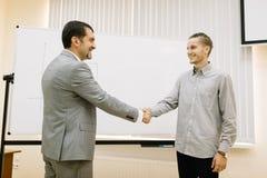 Homem de negócios maduro que agita as mãos com um estudante em um fundo borrado conceito da empresa de pequeno porte Imagens de Stock Royalty Free