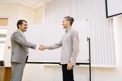 Homem de negócios maduro que agita as mãos com um estudante em um fundo borrado conceito da empresa de pequeno porte Fotos de Stock