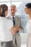 Homem de negócios maduro que discute com os colegas fêmeas imagem de stock