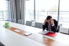 Homem de negócios maduro que sofre da dor de cabeça na tabela na sala de direção fotos de stock