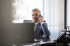 Homem de negócios maduro que usa o telefone celular na mesa no escritório fotografia de stock royalty free