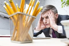 Homem de negócios maduro sobrecarregado que olha o portátil na mesa no escritório imagem de stock