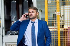 Homem de negócios maduro Speaking pelo telefone na fábrica imagens de stock royalty free