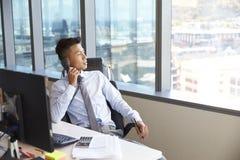 Homem de negócios Making Phone Call que senta-se na mesa no escritório fotos de stock