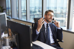 Homem de negócios Making Phone Call que senta-se na mesa no escritório fotografia de stock royalty free