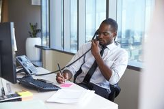 Homem de negócios Making Phone Call que senta-se na mesa no escritório imagens de stock