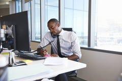 Homem de negócios Making Phone Call que senta-se na mesa no escritório foto de stock