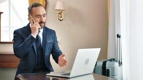 Homem de negócios masculino irritado que fala com o empregado subordinado que usa o smartphone que tem a viagem de negócios vídeos de arquivo