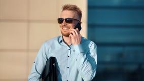 Homem de negócios masculino de riso alegre que aprecia a discussão usando o telefone celular no fundo da construção vídeos de arquivo