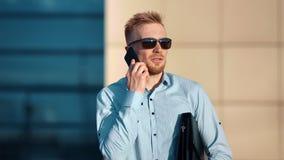 Homem de negócios masculino de sorriso nos óculos de sol que fala usando o tiro de meio da pasta da terra arrendada do smartphone vídeos de arquivo