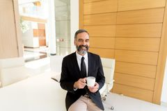 Homem de negócios de meia idade que tem a ruptura do coffe no escritório moderno imagens de stock royalty free