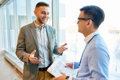 Homem de negócios moderno Chatting com colega imagens de stock