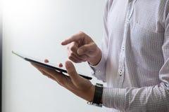 Homem de negócios moderno com notícia e trabalho da leitura do tablet pc com referência a fotos de stock