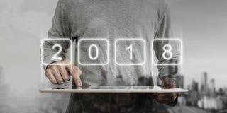 Homem de negócios moderno que aponta na tabuleta digital com holograma 2018 Ano novo, nova tecnologia e conceito novo do desenvol Fotografia de Stock