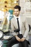 Homem de negócios moderno que senta-se no 'trotinette' Fotografia de Stock Royalty Free